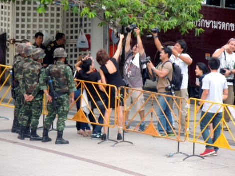 press reporters taking a photo of people taking a 'selfie' with some soldiers outside the Art and Cultural Centre